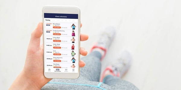 a woman checks her openfit app for new workouts
