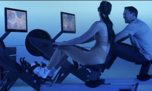 two people compete side by side their rowing machines